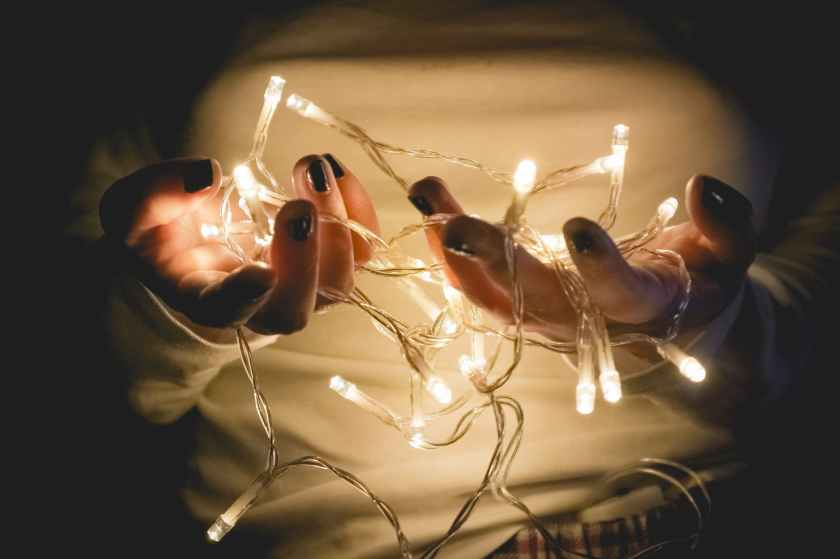 closeup photo of person wearing white long sleeved shirt holding turned on string lights